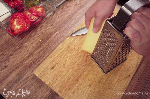 Снимите сливочный соус с огня и отставьте в сторону. Спелые помидоры нарежьте кружочками. Сыр натрите на терке.