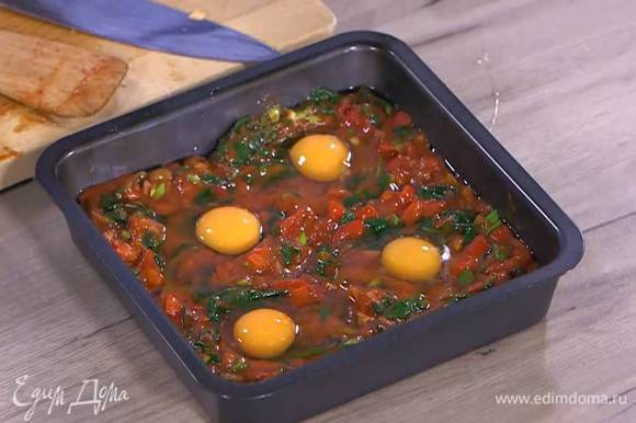 Небольшой глубокий противень смазать оставшимся оливковым маслом, равномерно выложить обжаренные овощи, сделать в каждом углу формы небольшое углубление и разбить в каждое по яйцу.