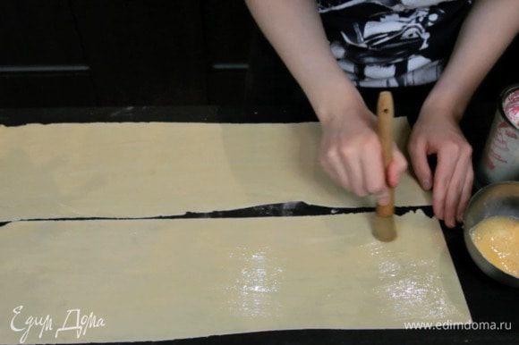 Нарезать на одинаковые полоски и смазать взбитым яйцом.