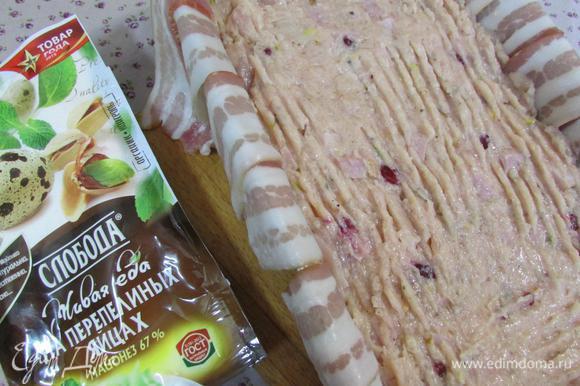 Форму для кекса застелить полосками бекона так, чтобы края свешивались. Выложить куриную массу, полностью заполняя форму, и слегка придавить.