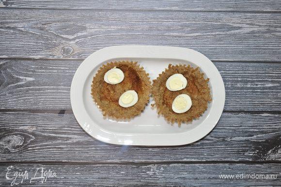 Перепелиные яйца заранее отварите, разрежьте пополам и уложите на дно тарталеток.