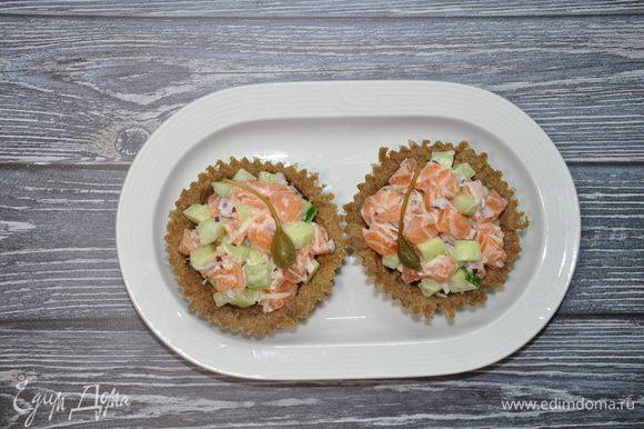 Затем на перепелиные яйца выложите готовый салат и украсьте, например, каперсами. Приятного аппетита!