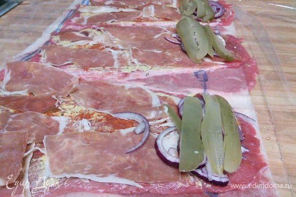 Выложить немного лука, нарезанного полукольцами, и слайсы огурца (подойдет соленый, маринованный, на ваш вкус).