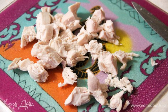 Отварить куриную грудку, дать ей остыть, а затем нарезать кубиками.