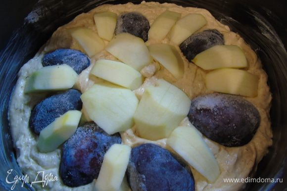 Форму 24 см смажьте маслом и выложите тесто. Сверху выкладываем сливы (у меня замороженная) и яблоки, которые предварительно очистите и нарежьте средними кусочками.