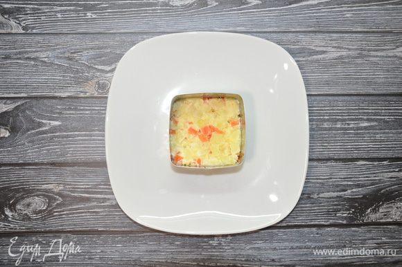 В формовочное кольцо выложите слой из картофельно-морковного салата, утрамбуйте ложкой.