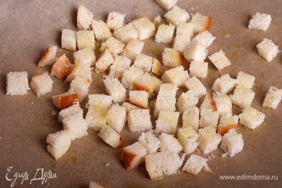 Ломтики батона нарезать на кубики и сбрызнуть оливковым маслом.
