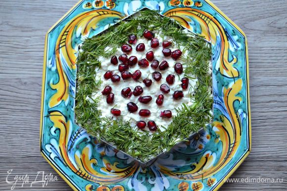 Верх салата украсьте укропом. Можно дополнительно украсить зернами граната или помидорами черри. Салат охладите и дайте настояться в течение 1 — 2 часов.