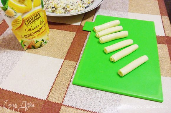 Для свечей воспользуемся пластинками сыра для бутербродов. Аккуратно скатать в трубочку и установить равномерно в кольцо.