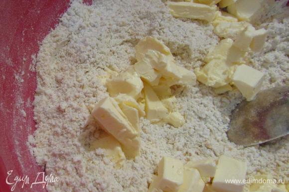 Сливочное масло комнатной температуры порезать небольшими кусочками и добавить к муке.