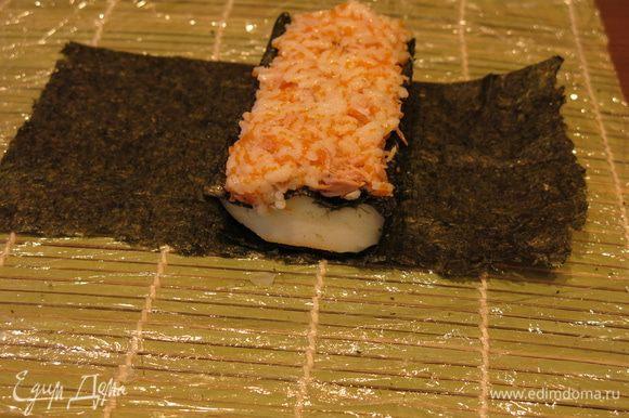 Кладем кальмар поперек на половинку листа нори (кусочек 1). Выкладываем на него рис, тщательно заполняя полости в «зубцах скорлупы».