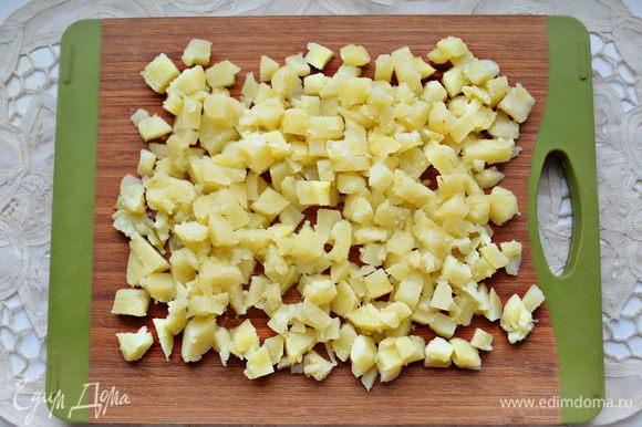 Картофель отварите «в мундире» до готовности, охладите, почистите и нарежьте кубиками.