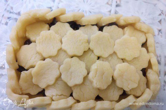 1 часть раскатать в пласт, уложить в форму для запекания. 2 часть раскатать, вырезать формой для печенья цветы. Из цветов сделать бока пирога. Вишню выложить на пирог. Верх пирога уложить цветочками. Запекать в разогретой до 180°С духовке, 15 минут.
