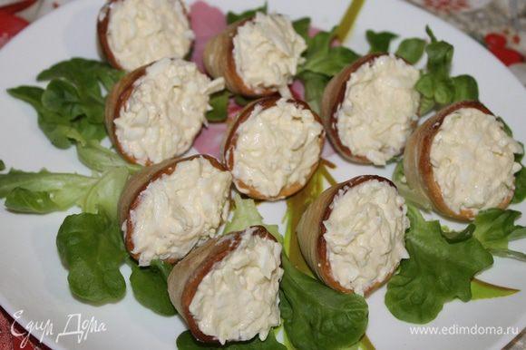 Заполните приготовленные ракушки-тарталетки салатом, украсьте зернышком граната или как вам пожелается, и разложите на листья салата.