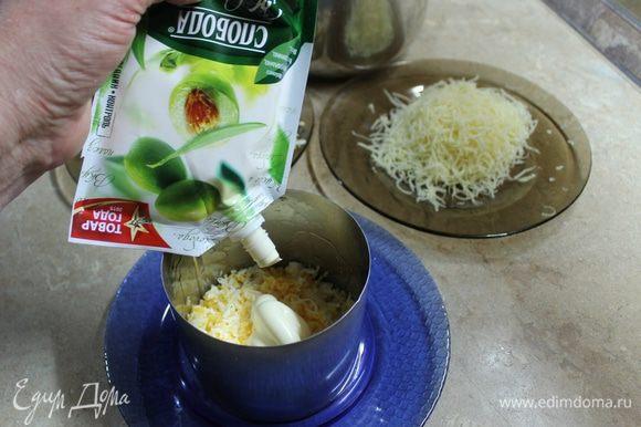 Салат можно собрать в большом салатнике, но порционная подача наряднее. В кулинарное кольцо первым слоем положите яйца, посолив по вкусу, сверху нанесите тонкий слой майонеза. Следующим слоем кладется лук, который нужно отжать от маринада. На каждый последующий слой наносите майонез.