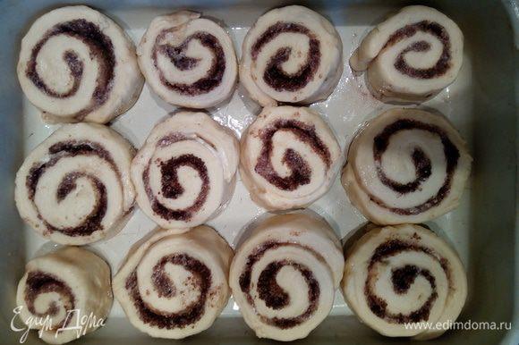Получившийся рулет разрезать на 12 приблизительно одинаковых кусочков. Выложить их в смазанную растительным маслом форму не вплотную друг к другу. Накрыть форму пищевой пленкой и оставить на расстойку на 30 минут.