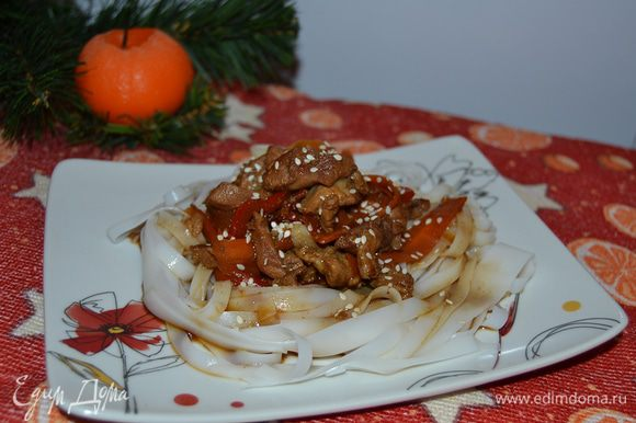 Лапшу выложить на тарелку в форме гнезда, в центр положить мясо с овощами, полить лапшу образовавшимся соусом. Посыпать семечками кунжута. Подавать сразу.