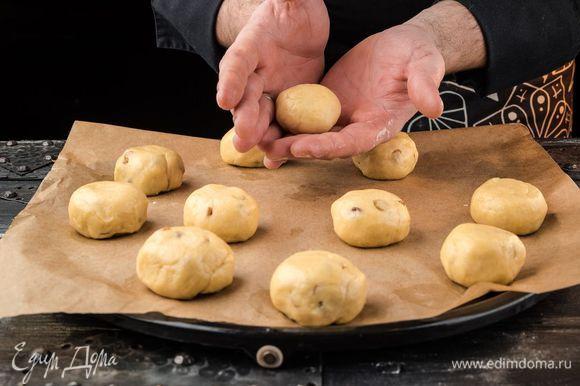 Выложить тесто на присыпанную мукой доску, руками распределить в пласт, затем сложить его пополам и еще раз пополам. Сформировать булочки.