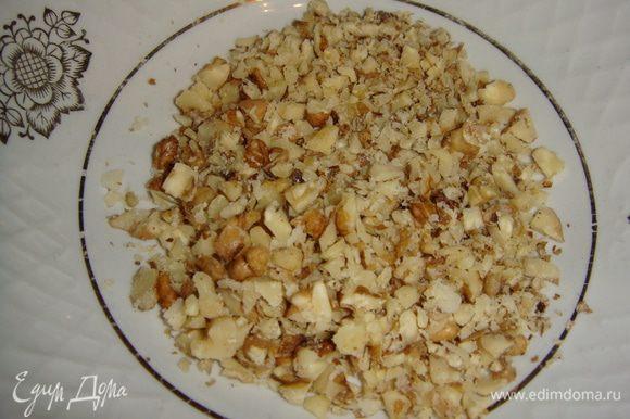 Грецкие орехи порубить ножом, добавить к остывшим грибам и перемешать.