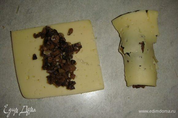 На кусочек сыра выкладываем грибы и сворачиваем в рулетик. Можно сыр нарезать брусочками. Я делала и так, и так, вкус от этого не меняется.