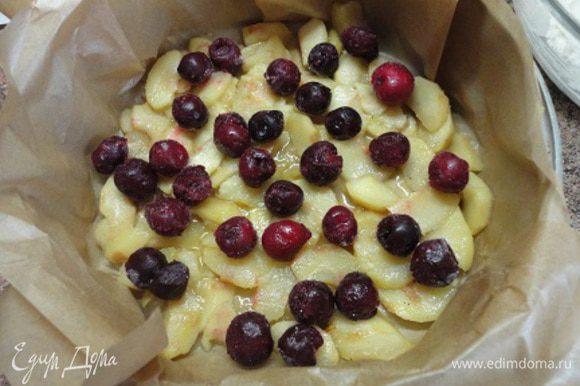 Разъемную форму выстилаем пекарской бумагой и выкладываем яблоки, а сверху ягоды. Лучше не размораживать. У меня вишня была такой крупной, не верится, что тут две горсти. Но это так.