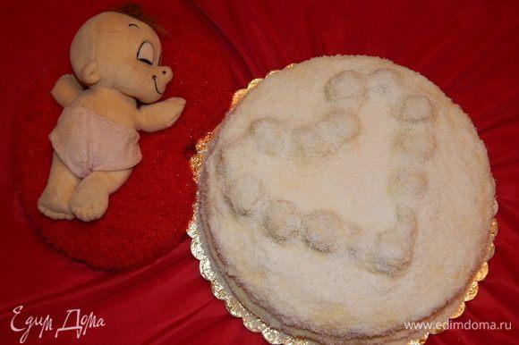 С торта снять кольцо. Можно выложить конфеты «Рафаэлло» в форме сердца на торте. А можно из остатков бисквита скатать шарики и ими выложить сердце. Смазать торт оставшимся кремом и посыпать кокосовой стружкой. Убрать торт в холодильник на ночь.