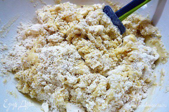 Добавляем в мучную смесь взбитые с сахаром яйца и вымешиваем тесто руками до однородной консистенции.