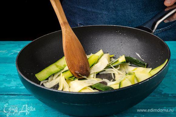 Цукини режем тонкими пластинами, лук — тонкой соломкой и обжариваем на оливковом масле на отдельной сковороде.