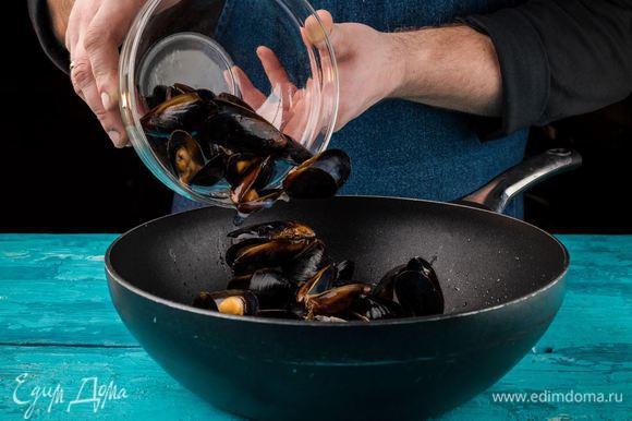 Добавить раскрывшиеся мидии в сковороду.