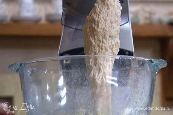 Цельнозерновую муку и 300 г пшеничной муки просеять, поместить в чашу комбайна, всыпать дрожжи, соль и перемешать все насадкой-крюком, затем, не выключая комбайна, влить теплое молоко с водой и вымешать тесто.