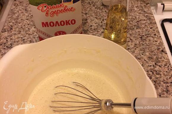 Молоко «Домик в деревне» довести до кипения и влить тонкой струйкой в тесто, непрерывно взбивая венчиком. Затем добавить растительное масло и еще раз хорошо взбить.