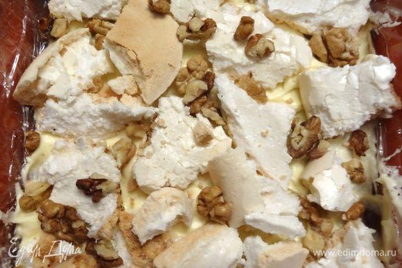 Форму выстелить пищевой пленкой. На дно выложить 3 — 4 ложки крема (1/4 часть), сверху — кусочки меренги (1/3 часть) и щедро посыпать орехами. Чередовать слои, последний слой — крем. Поставить торт в морозильник на несколько часов.