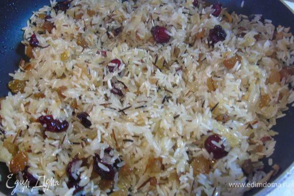 В сковороду к жареному луку добавляем рис, чернику сушеную (у меня изюм и клюква), корицу в палочках и, посолив и поперчив по вкусу, обжариваем немного, все время помешивая.