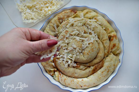 Круглую форму смажьте маслом и выложите по кругу в виде улитки блинные рулетики. Сверху посыпьте тертым сыром.