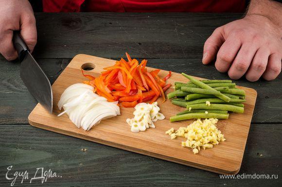Нарезать лук, чеснок и имбирь тонкими кружочками. Болгарский перец нарезать полосками, фасоль разморозить и промыть.