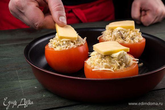 Выложить помидоры на противень, положить сверху кусочки сыра.