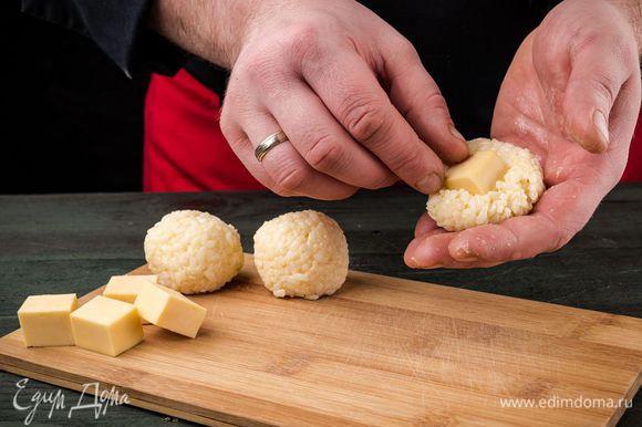 Из рисовой массы влажными руками сформировать шарики, поместив внутрь каждого квадратик мягкого сыра.