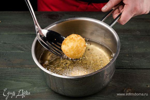 Разогреть в сотейнике оливковое масло и обжаривать шарики со всех сторон до появления золотистой корочки, а затем выкладывать на бумажное полотенце, чтобы убрать излишки жира.