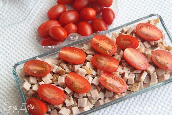 Помидоры черри разрезать на половинки и добавить в салат.