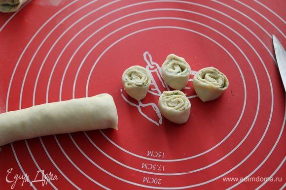 Тесто раскатать в пласт, нанести масляную начинку, свернуть тесто в рулет, затем нарезать его на небольшие кусочки.