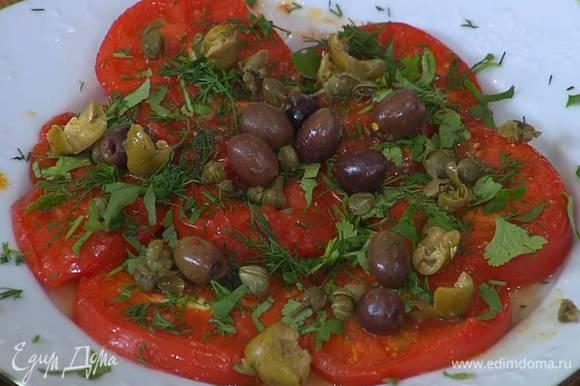 Каперсы и оливки измельчить руками и посыпать помидоры с зеленью.