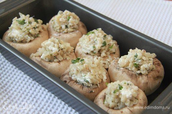 Форму смазать маслом. Наполнить шампиньоны начинкой из перловой крупы с сыром. Выпекать в предварительно разогретой до 200°С духовке 15 минут.