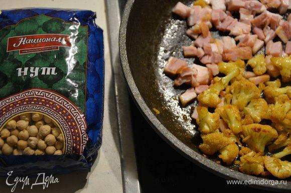 К капусте добавить мелко нарезанный бекон, поперчить и жарить еще 2-3 минуты.