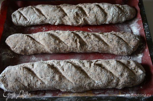 Перевернуть багеты на противень, застеленный пергаментом или силиконовым ковриком, сделать надрезы.