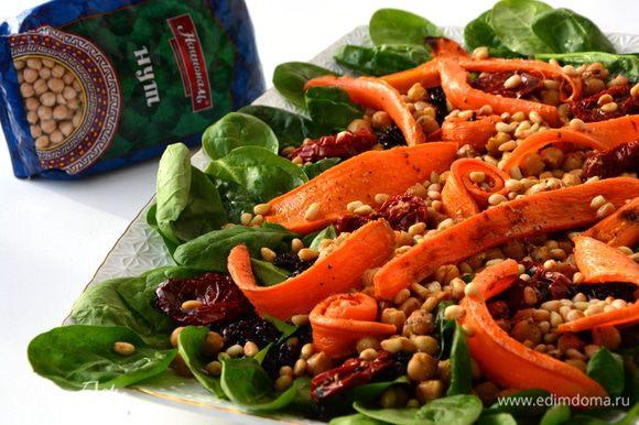 Сервировка: выложить шпинат (предварительно помыть и просушить), затем сверху черный рис, по центру вдоль выложить нут, местами добавить вяленые томаты, сверху — печеную морковь и посыпать все кедровыми орешками. Полить заправкой и подавать к столу. Приятного аппетита!