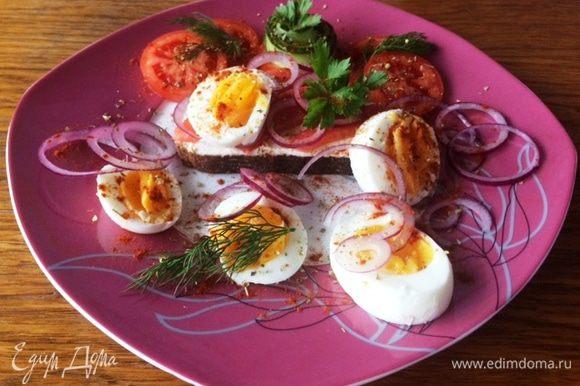 Поверх рыбки укладываем колечки красного лука. Режем произвольно вареные яйца. Подаем с помидорами, особенно вкусно с помидорами-черри. Сверху я присыпала немного орегано сухим и сладкой копченой паприкой. В завершение композиции украшаем листиками петрушки. Вкусный бутерброд к завтраку с красной рыбкой, варенными яйцами и помидорами. Приятного аппетита! Побалуйте своих близких.