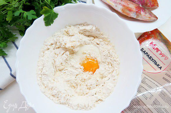 Делаем углубление в мучной смеси, добавляем яйцо и теплое молоко. Замешиваем тесто.