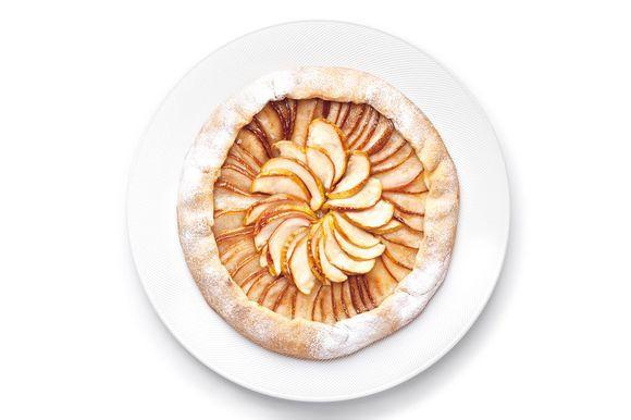 Тесто раскатайте на присыпанной мукой поверхности в круг толщиной 4 мм. В центр круга выложите ломтики яблок и груш внахлест, отступив от края 2–3 см. Затем аккуратно подверните края на начинку. Присыпьте фрукты тростниковым сахаром. Выпекайте пирог при температуре 190°С в течение 40–45 минут. Украсьте пирог веточкой мяты и подавайте с мороженым.