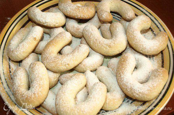 Достать печенье из духовки и посыпать еще горячим сахарной пудрой.