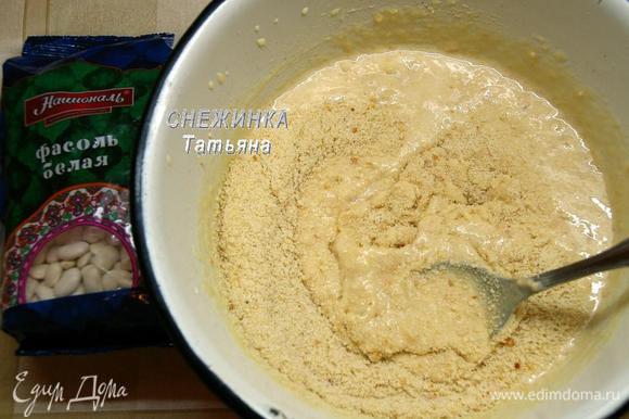 К желткам добавляем фасоль, перемешиваем. Затем соединенные с разрыхлителем измельченные сухари. Очень хорошо перемешиваем.